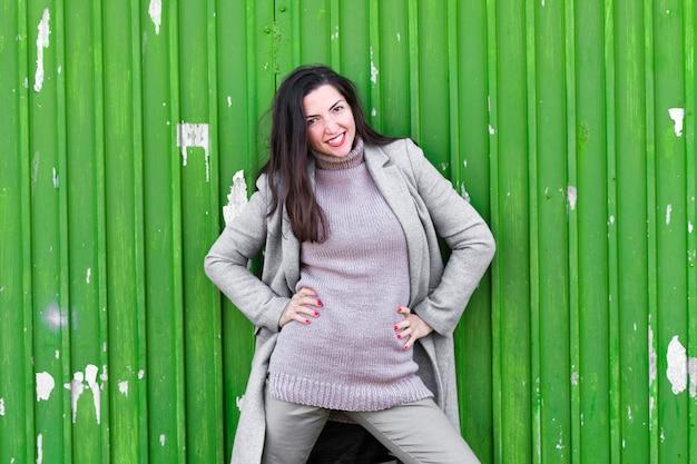 Девушка на зеленой промышленной двери. в теплом сером пальто. портрет красивой девушки на зеленой промышленной двери