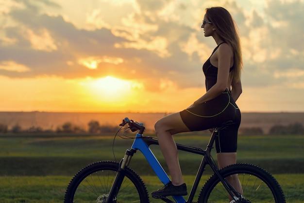 Девушка на горном велосипеде по бездорожью, красивый портрет велосипедиста, фитнес-девушка катается на современном горном велосипеде из углеродного волокна в спортивной одежде.