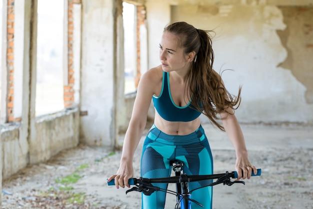 オフロードのマウンテンバイクの女の子雨天のサイクリストの美しい肖像画フィットネスの女の子