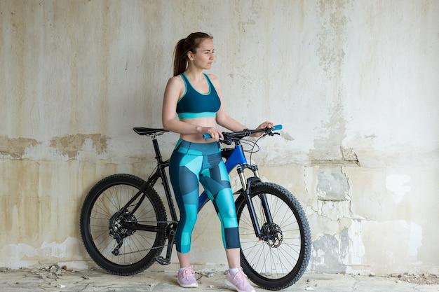 비오는 날씨에 자전거 타는 사람의 아름다운 초상화 오프로드에서 산악 자전거를 탄 소녀