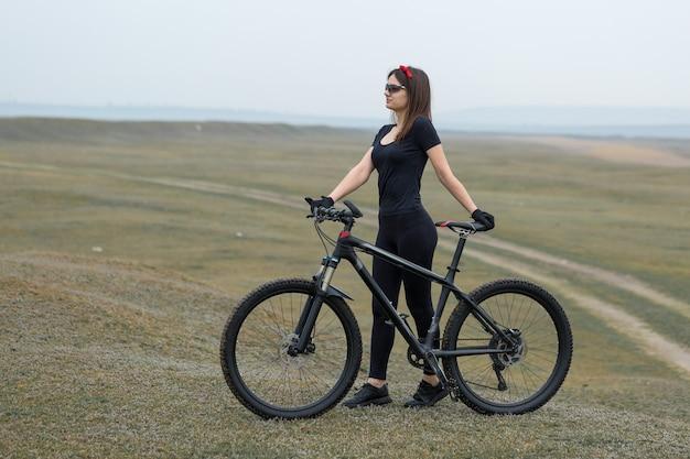 雨天のサイクリストのオフロードの美しい肖像画のマウンテンバイクの女の子
