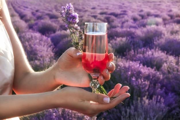 ピンクのワインと花束のグラスとプロヴァンスのラベンダー畑でピクニックの女の子