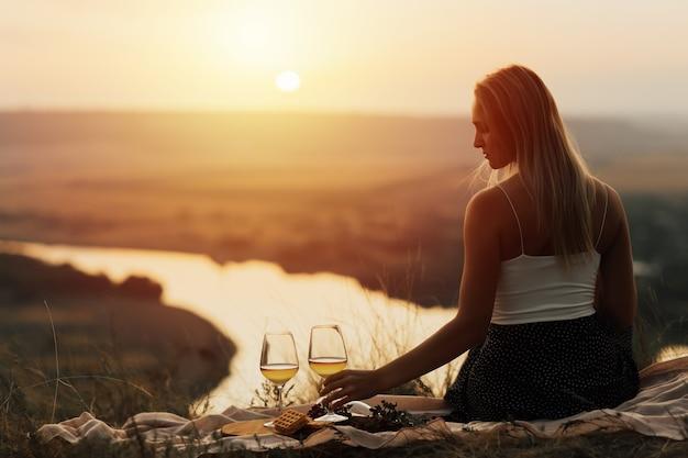 カメラに背を向けてピクニックをしている女の子。日没時の山での屋外ピクニックの概念。