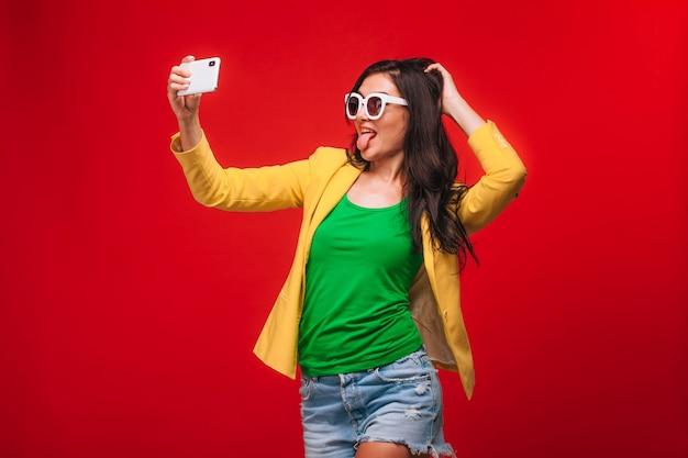 ジャケットの赤い背景の女の子が電話で自分撮りをします
