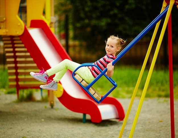 Девушка на качелях на детской площадке в летнее время
