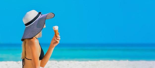 Девушка на тропическом пляже с мороженым premium фотографии