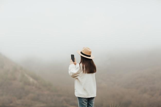 관점에 소녀는 안개 산의 사진을 찍고있다.