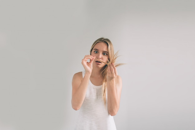 머리 문제와 흰색 배경에 소녀. 금발 여자는 흰색에 고립 된 셔츠를 입고있다.