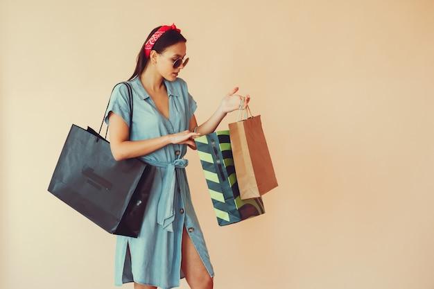 쇼핑백과 노란색 벽에 여자