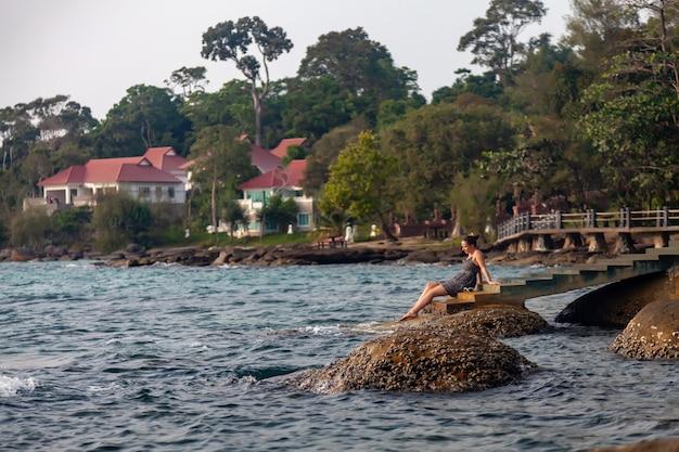 해질녘 열 대 바다의 배경에 소녀입니다. 여름 옷을 입은 여자가 독에 앉아 있다. 여행이 그리워요. 여행. 꿈의 여성. 야자수와 바다를 배경으로 하는 해변에서의 여름 생활 방식