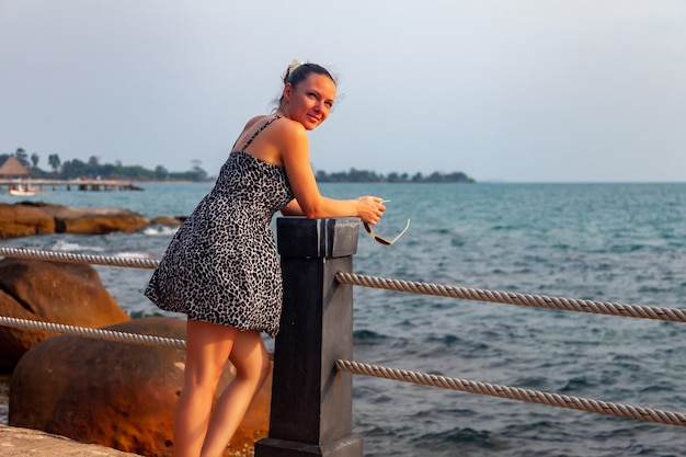 해질녘 열 대 바다의 배경에 소녀입니다. 여름 옷을 입은 여자는 울타리에 서 있다. 그리워. 여행을 놓쳤습니다. 꿈꾸는 여성. 전망대와 바다를 배경으로 하는 해변의 여름 라이프스타일