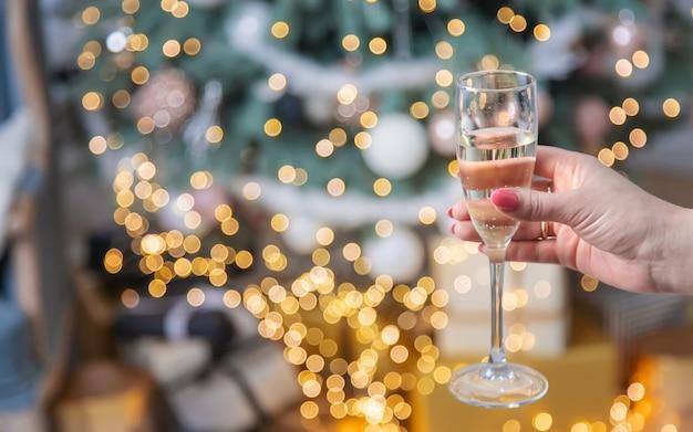 Девушка на рождественском фоне с шампанским. выборочный фокус. праздничный день.