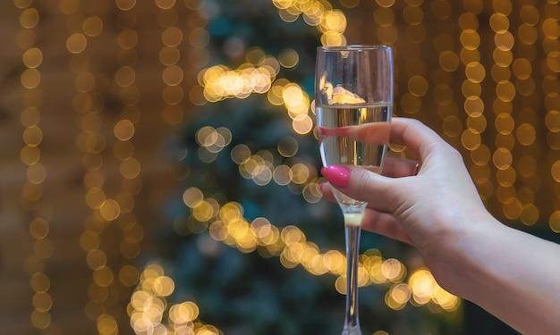 シャンパンとクリスマスの背景の女の子。セレクティブフォーカス。ホリデー。