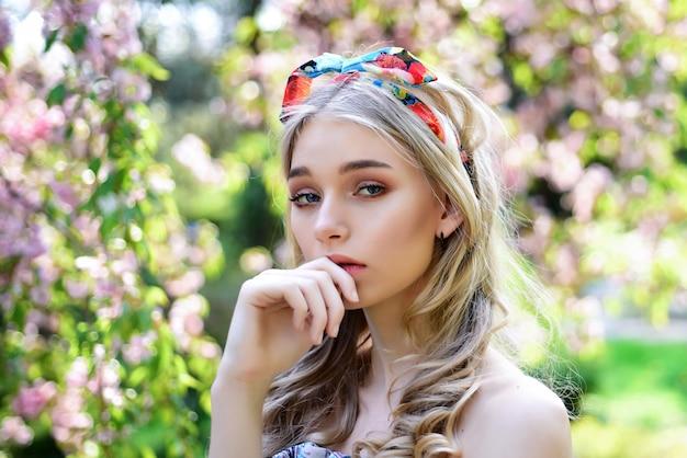 夢のような思いやりのある顔の女の子、桜の花の近くの優しいブロンド、自然の背景。春咲きのコンセプト。晴れた春の日に公園で若い女性。頭にショールを持った若い女性は自然を楽しんでいます。
