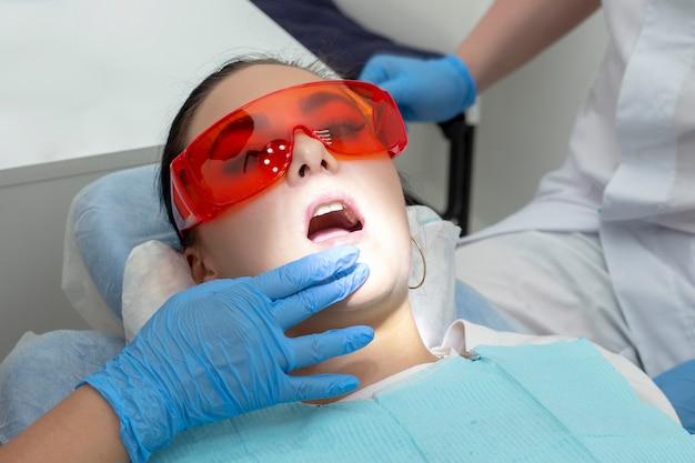 Девушка на осмотре у стоматолога. лечение кариозного зуба. врач использует зеркало на ручке и бортовой аппарат