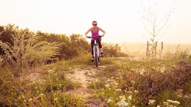 Девушка на горном велосипеде едет по тропе на красивый восход солнца.