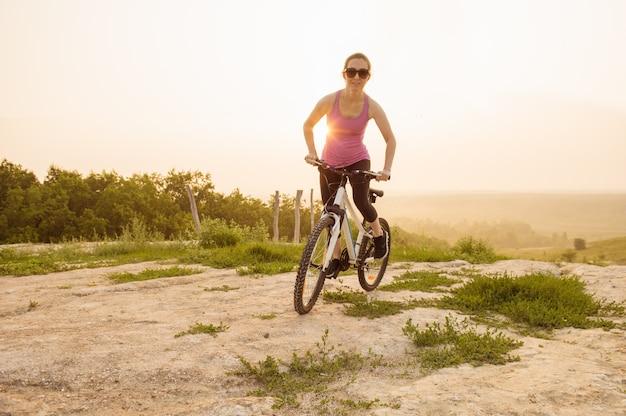 산악 자전거에 소녀는 아름 다운 일출에 흔적에 탄다.