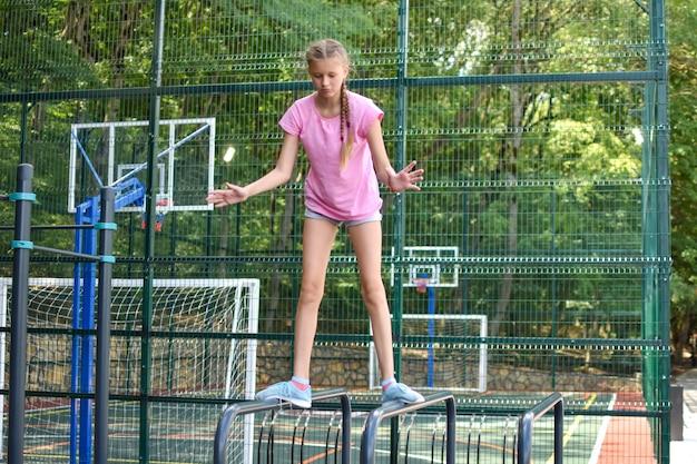 Девушка на открытом спортивном поле. девушка-подросток делает гимнастические упражнения в тренажерном зале на открытом воздухе.