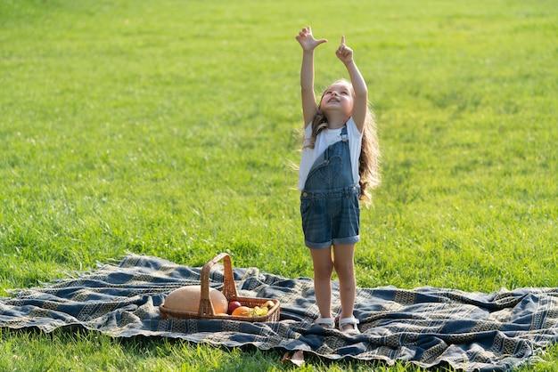 ピクニックの女の子。日当たりの良い公園や庭でバスケットを持つ子供の幼児。