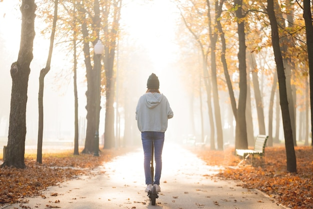 秋の公園でスクーターに乗る女の子