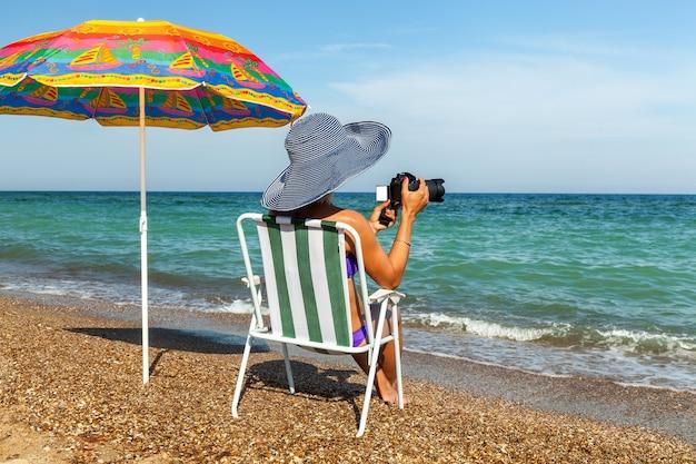 Девушка на пляже, загорающая девушка с ноутбуком, женщина под зонтиком