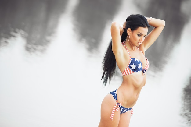 미국 국기와 함께 해변에서 여자