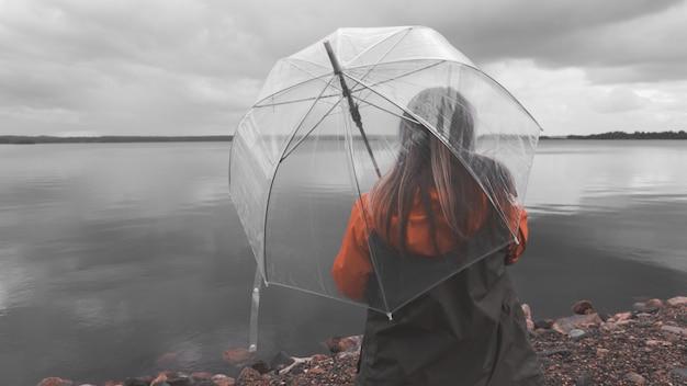 Девушка на озере с зонтиком в плохую погоду