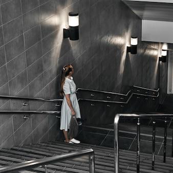 階段を下りて、トランジションが遅く、地下鉄に乗っている女の子。地下道への降下中の一人。