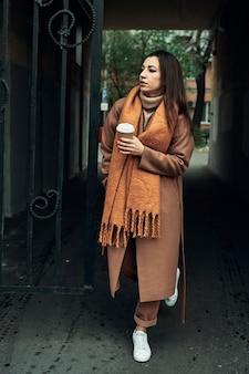 Девушка на улице с одноразовым бумажным стаканчиком. уберите еду, погуляйте по городу.