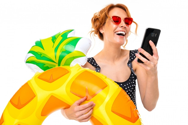 スマートフォンでインターネットに座っている水泳サークルで海辺での休暇の女の子