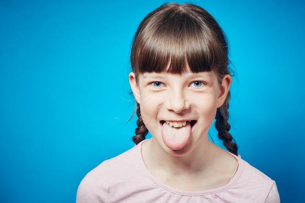 舌を突き出て黄色の背景の女の子。かわいいおどけと戯れるコンセプト