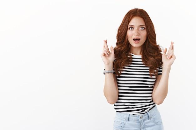 女の子は畏敬の念と興奮で口を開け、祈っている間驚いたように見えます。かわいい赤毛の女子学生が指を交差させて、ウィッシュパス試験が最高のスコアを獲得するようにします。重要なニュースを待つことを願っています