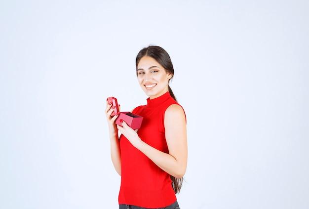 소녀는 빨간색 선물 상자를 열고 행복하다고 느낍니다.