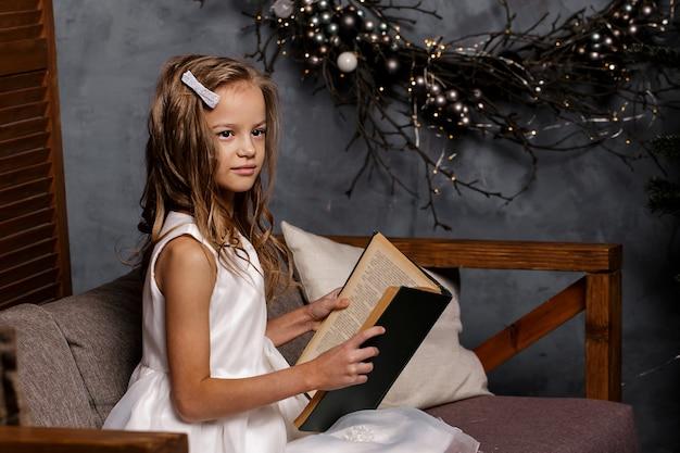 Девушка открывает книгу в комнате, украшенной на рождество