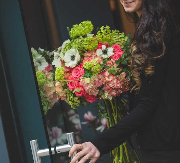 Girl opening the door with a bouquet of multiple flower types in another hand