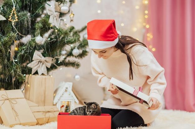 子猫とギフトボックスを開く女の子。クリスマスのサプライズ。