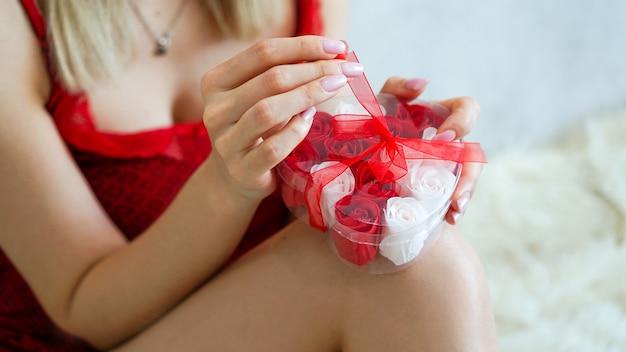 Девушка открывает подарок, наслаждаясь подарком дома, романтическими отношениями. день святого валентина, концепция любви и счастья
