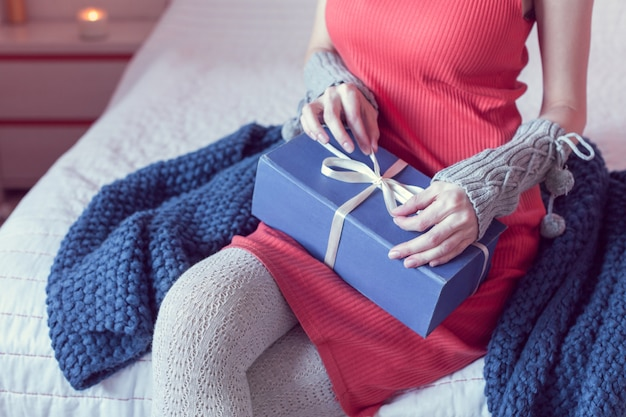 Девушка открывает подарок сидя на кровати