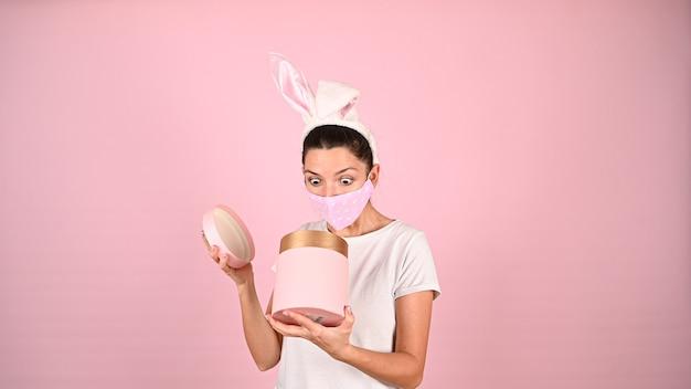 Девушка открывает подарок ушками в маске. фото высокого качества