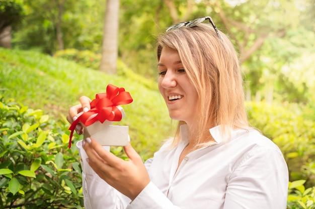 Девушка открывает подарок. женщина в белой рубашке держит подарочную коробку с красным бантом