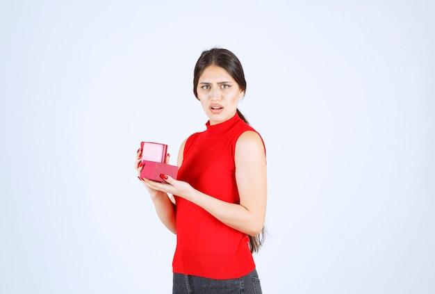 Девушка открывает красную подарочную коробку и выглядит недовольной.