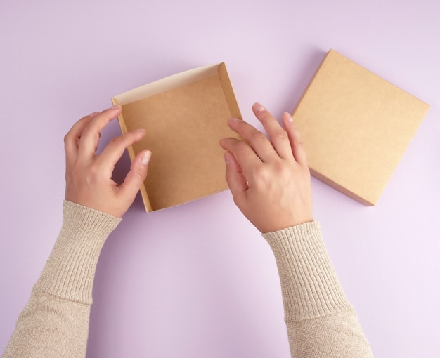 Girl opens a brown square box on a purple background