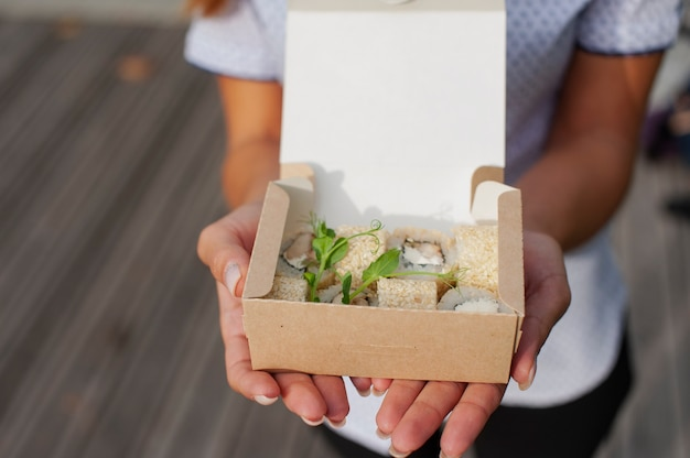 The girl opens a cardboard bag with a set of sushi. seafood delivery concept.