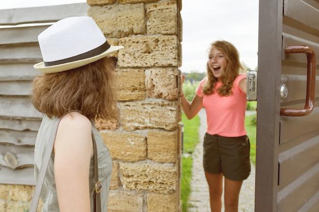 女の子は彼女の友人に正面玄関を開きます