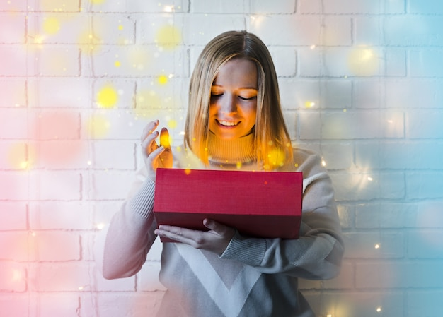 Girl opens the gift and wonders. glowing garland. miracle