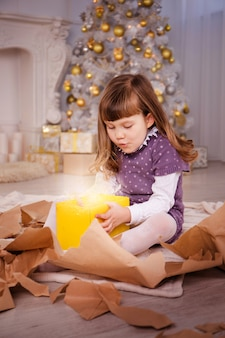 Девушка открывает подарки возле елки