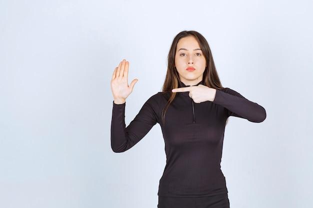 소녀는 한 손을 열고 다른 손으로 가리 킵니다.