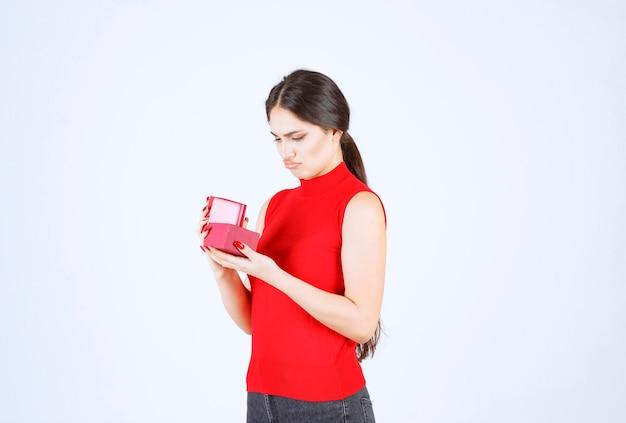 La ragazza apre una confezione regalo rossa e sembra insoddisfatta.
