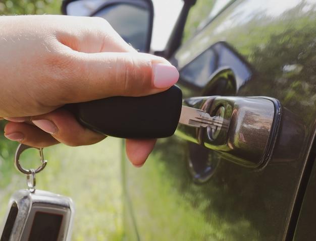 Девушка открывает машину ключом крупным планом