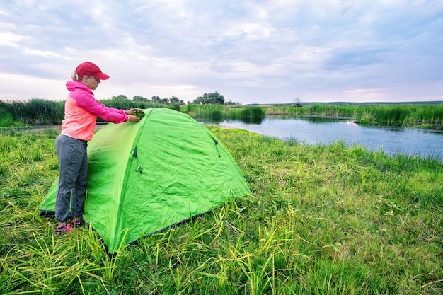 Девушка открывает окно палатки